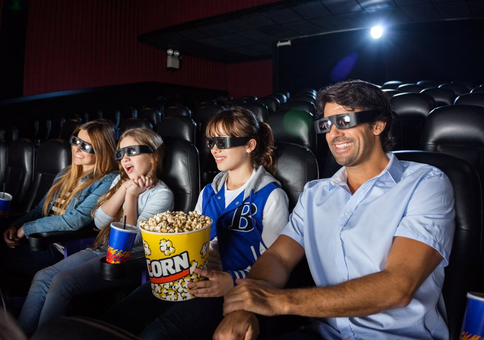 Happy family of four having snacks while watching 3D movie in cinema theater