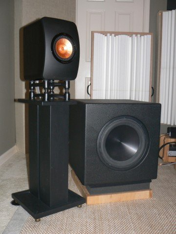 kef ls50. and make sure the amp you buy can accommodate this setup. then run subs at a higher frequency get more of that mid bass punch. kef ls50