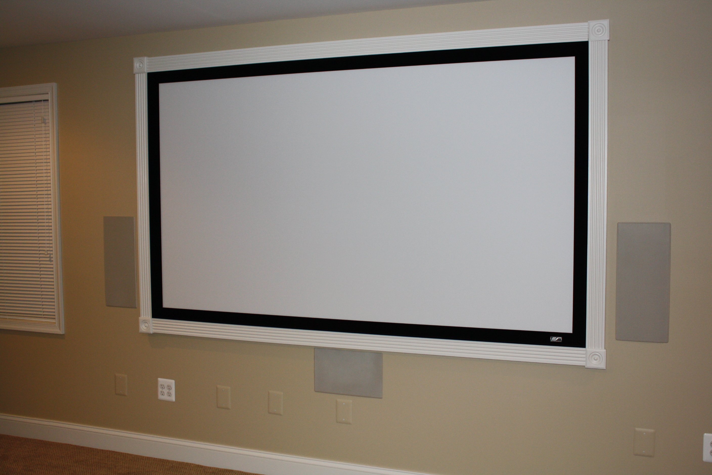"100"" Elite (Sable) fixed mount screen (Polk Vanishing Series painted-to-match grilles on). Fluted casing and Rosettes installed after mounting."
